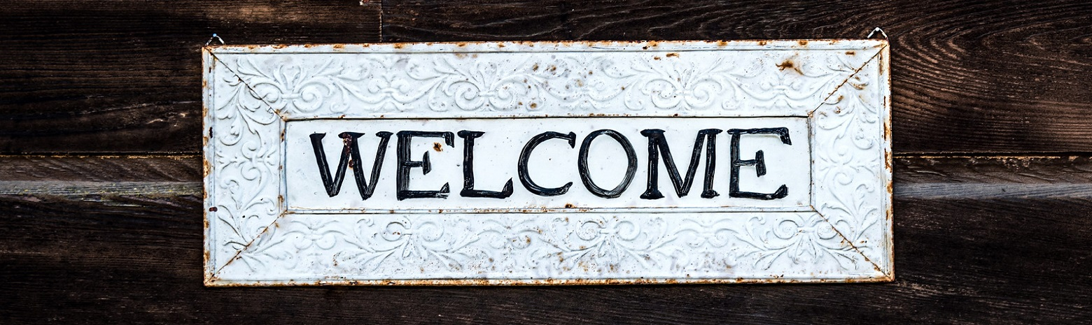 Metal Welcome Sign with dark wood background