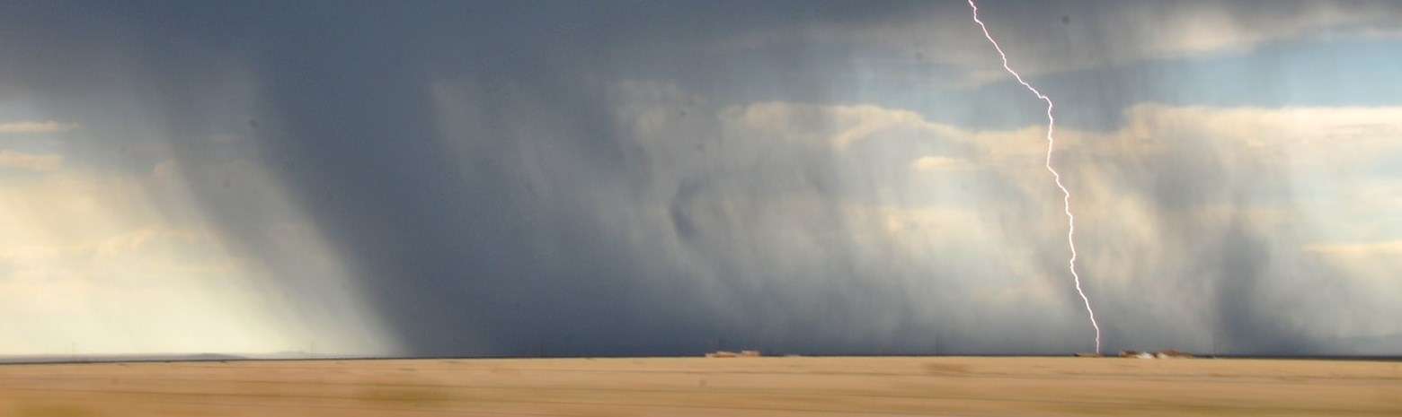 Dark funnel cloud with lightening strike in wheat field