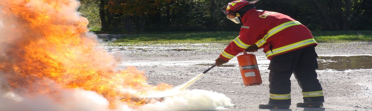 Fire fighter using fire extinguisher to put out a fire