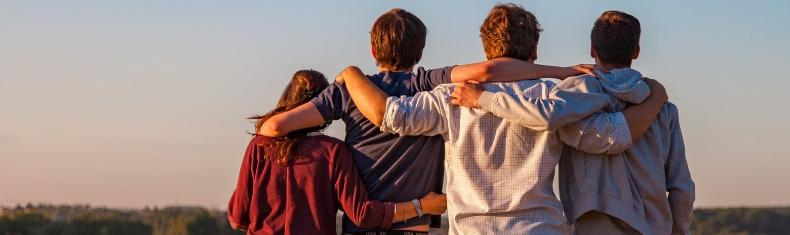Four teenagers with arms over each others shoulders  standing in farmers field