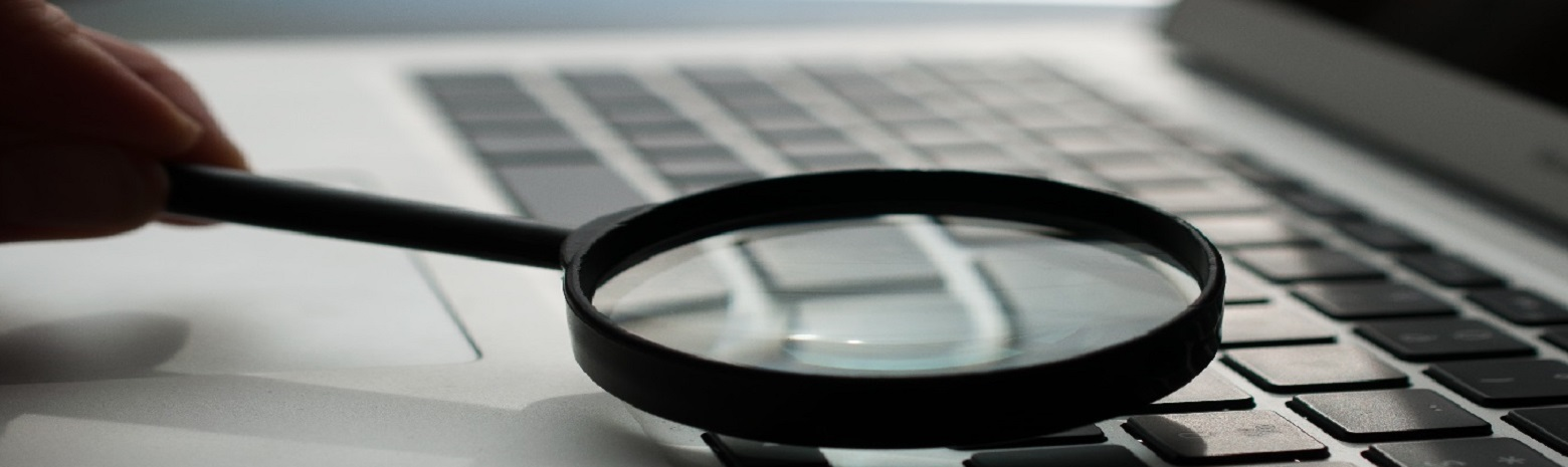 Magnifying glass near grey laptop